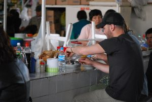 A tourist eating Chicken Soup in San Pedro Market