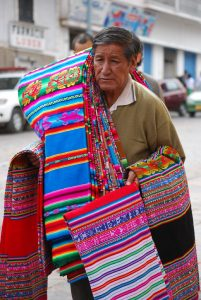 A Man Porting Carrying Cloths (Queperinas) while Selling in the Streets of Cuzco