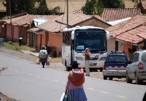 Tourist taking Picture of Local Woman by Houses Scheduled for Demolition by Sacsayhuaman