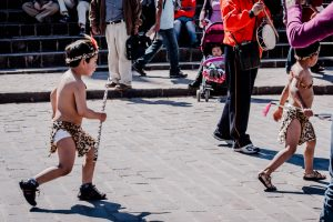Boys run through the streets of Cuzco in jungle garb (Photo Arnold Fernandez)