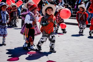 A group of boys dressed as cholo qorilazos carry balloons through the streets of Cuzco (Photo Arnold Fernandez)