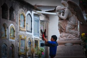 A Boy Cleaning a Grave in Almude Cemetery (Photo: Walter Coraza. M)